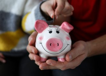 Close-up view of mans hands holding piggy-bank. Woman putting coin and saving-up money. Financial planning and checking expenses. Family budget concept