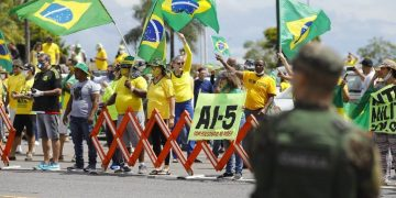 Supporters of Brazilian President Jair Bolsonaro demonstrate against quarantine and social distancing measures imposed by governors and mayors to combat the new coronavirus outbreak and demand military intervention (AI-5) in Brasilia on April 19, 2020. (Photo by Sergio LIMA / AFP)